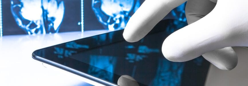 hand in medical blue glove touching modern digital tablet on x-ray images background. Concept of medical or research theme