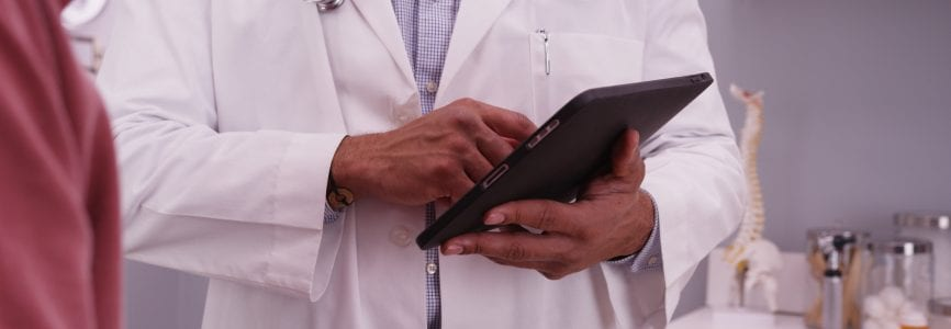 Portrait of male black doctor using tablet device with an elderly patient.