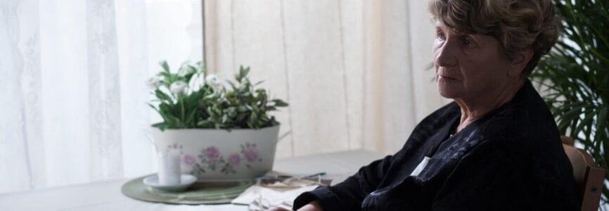 Sad elderly lady in black with a handkerchief