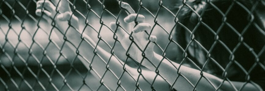 prison women in the cage hand at fence prison in jail, no freedom struggle concept with grain texture.