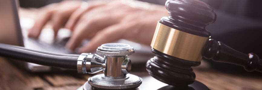 Close-up Of Stethoscope And Gavel On Wooden Desk