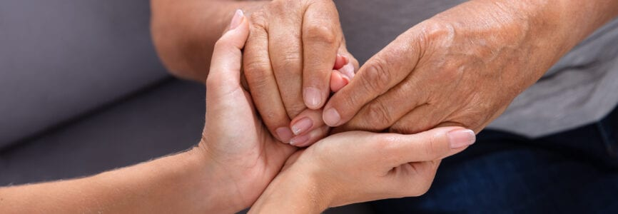 Close-up Of A Daughter Holding Her Elderly Father's Hand