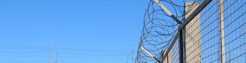 Barbed wire on the fence, concept for the protection of territory, property, military installations, the US and Mexico Border or places of detention, wide view against a blue sky.