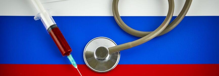 Stethoscope and syringe on Russia flag with coronavirus label