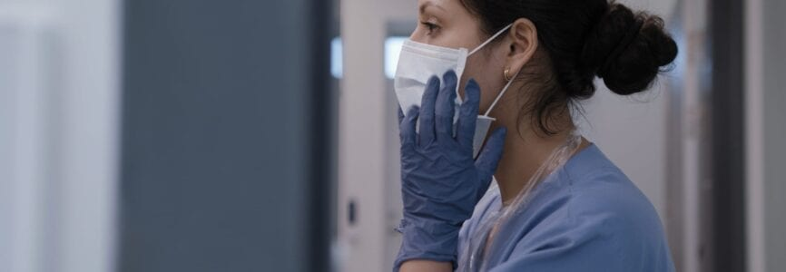 Nurse fixing surgical mask in infection room and preparing for treating corona virus.
