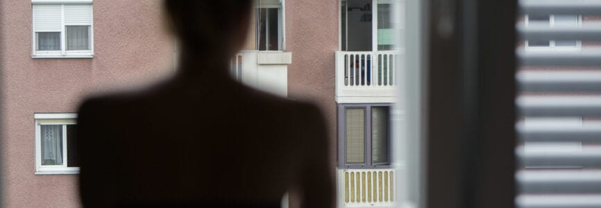 Home quarantine and social distancing during covid pandemic. Silhouette of lonley caucasian woman standing by window, anxiously looking out. Coronavirus infection, pandemics, disease outbreaks.