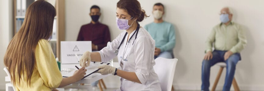 Mass vaccination of the population. Female doctor in a mask gives the patient documents to sign before giving her the Covid-19 antiviral vaccine. Background with people waiting in line for a vaccine.