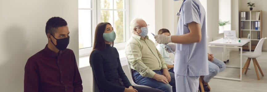 Young man doctor nurse in medical protective face mask talking to patients sitting and waiting in line before vaccination against covid-19 virus during pandemic in medical clinic office