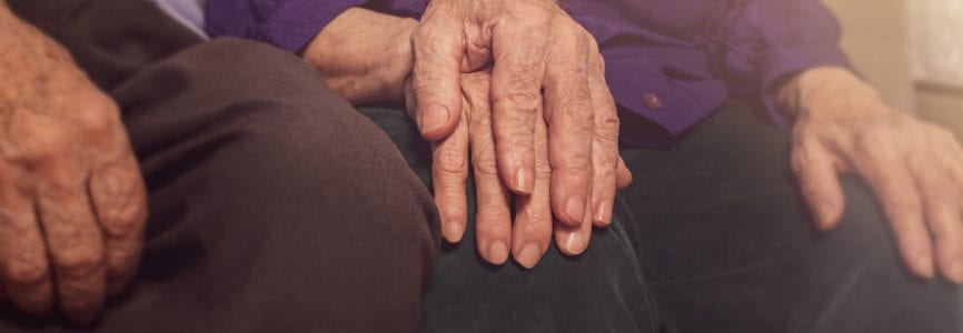 Elderly couple hands. Husband holding wife's hand for support. Nursing home. Age-related diseases. Love to the death.
