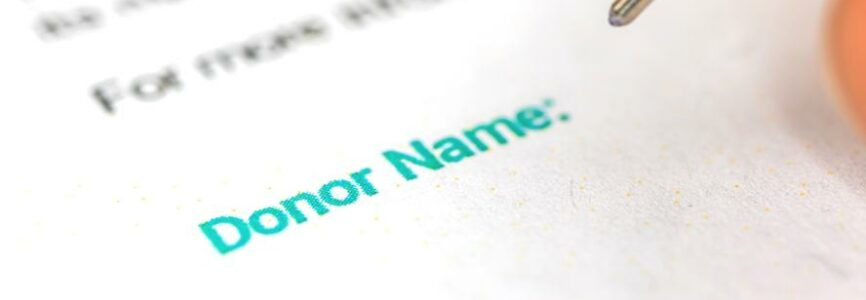 Donation form with donor name background, man is signature donation consent, charity concept photo