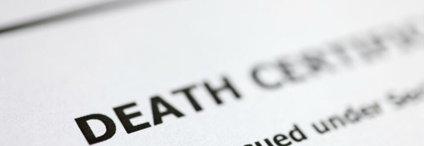 Death certificate is on table. Paperwork after death of relative concept