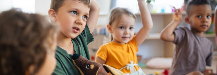 A group of small nursery school children sitting on floor indoors in classroom, raising hands.
