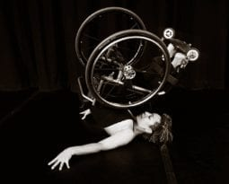 Alice Sheppard, in her wheelchair, rolls into a shoulder stand.