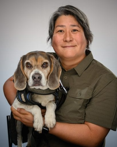 Karen Nakamura holds a beagle wearing a service dog vest in her arms. She has a relaxed smile on her face as both she and the dog gaze into the camera.