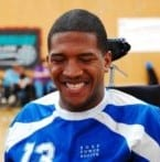 Lateef McLeod, a Black man wearing a blue jersey, is caught in the middle of laughing. His eyes are pressed shut and a smile stretches across his face.