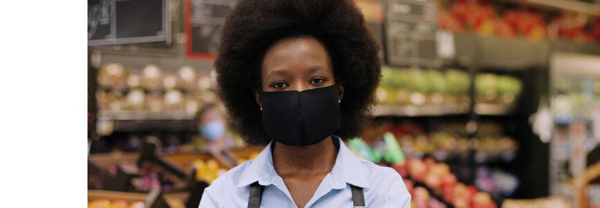 Close up portrait of happy African American female Worker in black mask and gloves standing in supermarket and looking at camera. Young woman food store assistant at work in quarantine