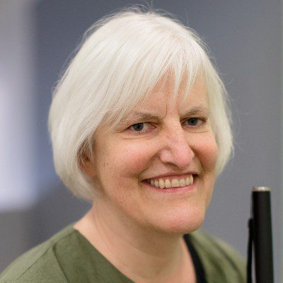 Georgina Kleege, a white woman with a short white bob haircut, beams at the camera with a wide smile, holding her white cane in front of her.