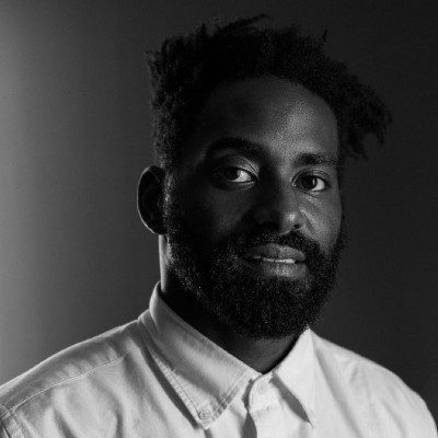 Black and white photo of Jerron Herman, a dark-skinned Black man with a beard, wearing a white button up looking into the camera with a slight smile. Photo by Fernando Villela