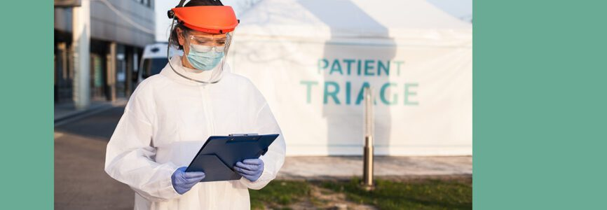Medical worker wearing PPE protective white suit,face shield mask,holding clipboard patient health check up form,standing in front of clinic hospital,triage tent for COVID-19 UK point of care testing