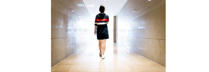 Woman walking down a corridor towards lit exit