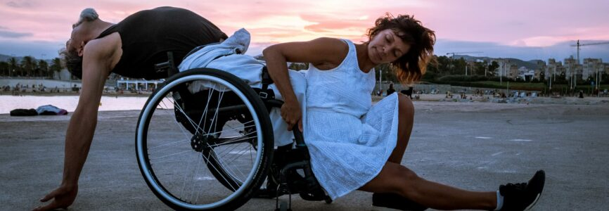 Two people dance under the sunset on a beach. On the left, a man leans back in his wheelchair with his arms dangling behind him, hands grazing the ground. In front of him, a woman grips the chair to press her back against his shins, stretching her own leg out in front of her.