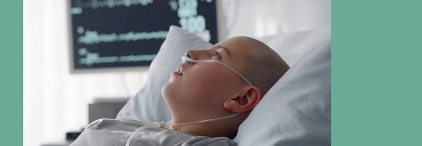 Sick child with cancer lying in hospital bed with nasal cannula. Close up portrait of bald teen boy patient resting in bed after chemotherapy treatment or surgery